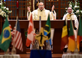 Flags representing a variety of countries where the Sisters of St. Mary of Namur have served are on display as Fr. Richard Flores, center, says the Eucharistic Prayer